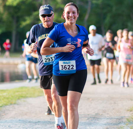 North Babylon, New York, USA - 8 July 2019: A runner racing in a 5K around a lake smiling for the camera on a summer evening wearing a patriotic blue shirt.