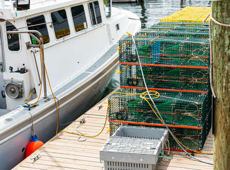 A fishing boat docked next to a wood pier with lobster and crab traps stacked on each other ready to be used.