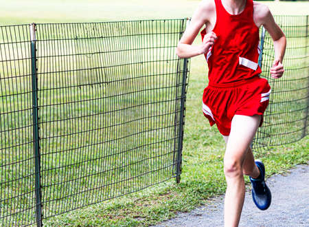 Selective focused is used to leave copy space in front of runner in red uniform running next to a wire fence during a high school cross country 5K race. Imagens