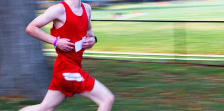 Panning to add blurred motion to runner racing in a red uniform passing a tree with a black fence and field in background and copy space in front of the runner runing in a 5K race. Imagens