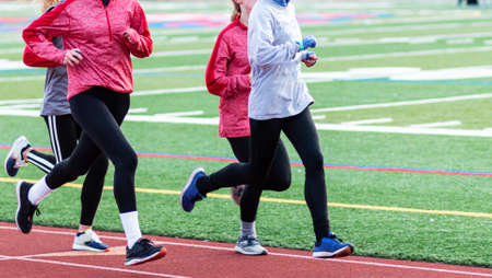 A group of high school girls running on a track wearing black spandex and long sleeves.