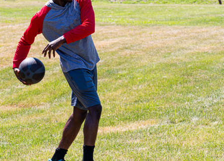African American male teenager throwing a medicine ball behind his back during track and field practice on grass.