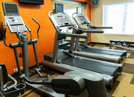 Two tredmills and one elliptical machine available to exercise on in a small gym.