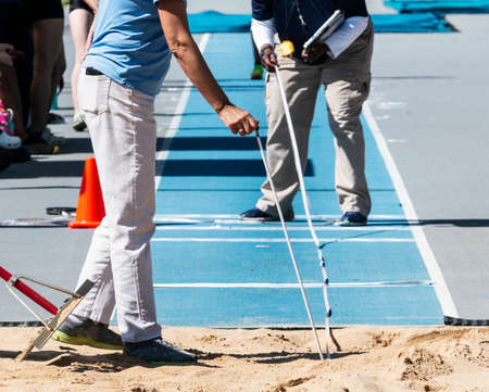 Track officials measuring the distance of an athletes jump in the sand pit with a blue runway outdoors.