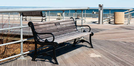 A park bench with a dedicated name plate on the boardwalk at Sunken Meadow State Park on a sunny March morning with the beach in the background. Imagens