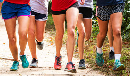 Close up of high school girls cross country team running together toward the camera on a dirt path in a park.