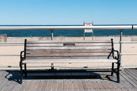 A park bench on the boardwalk of Sunken Meadow State Park with the beach and water in the background on a sunny March day.