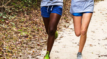Frint view of two girls running on a dirt path in a park wearing shorts, Imagens