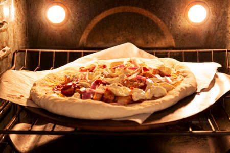 A homemade barbeque chicken pizza on a cooking stone cooking in the oven.