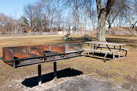 Triple barbeque grill in Sunken Meadow State Park with picnic tables on grass.