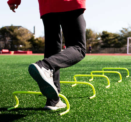 Close up of a high school track athlete is jumping on one leg over yellow mini babana hurdles on a green turf field at practice. Imagens