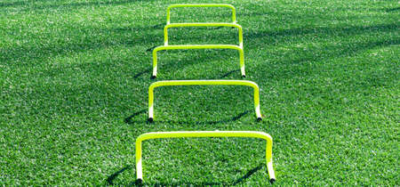 Five yellow mini banana hurdles in a row for runners to perform sports drills over during speed and agility practice.