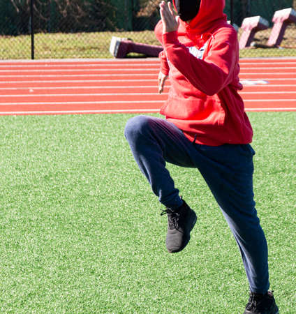 A high school track and field runner performing speed and agility drills on a green turf field during practice wearing a black face mask for protection.