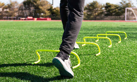 The feet of an athlete stepping over yellow mini banana hurdles set up aon a green turf field for sports training drills.