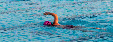 A female swimmer swimming in a pool alone training for a triathlon with her face down and one arm out of the water.