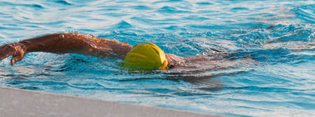 Close up of a man in a yellow bathing cap during his morning swim training for triathlons in a pool.