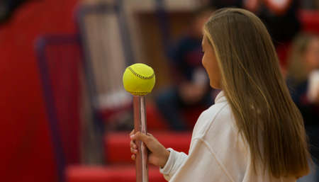 A high school girl is walking and balancing a yellow softball on a pink baton in a gym for fun and games. Imagens