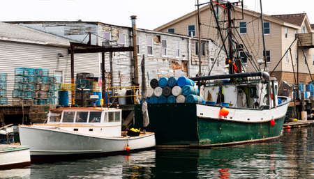 Commercial fishing boats docked behind buildings with colorful lobster traps, rope and everything they need to be ready to return to the sea the next day.