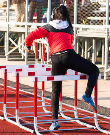 Rear view of a high school girl wearing headphones while warming up doing hurdle drills on an outdoor track next to the bleachers before her race.