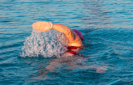 Water flowing off the arm of a female swimmer training for a triathlon in a pool early in the morning. Imagens