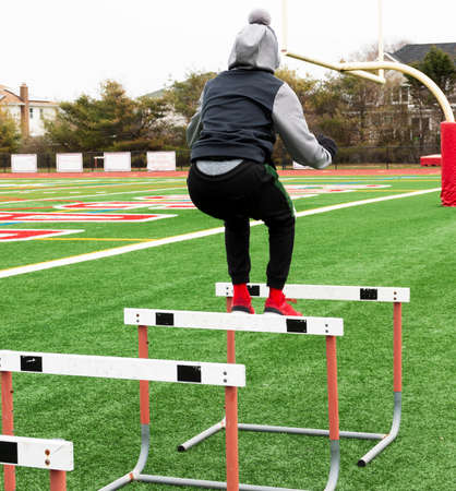 A high school boy at track practice is jumping over a row of hurdles set up for strength and agility practice on a gree turf field.