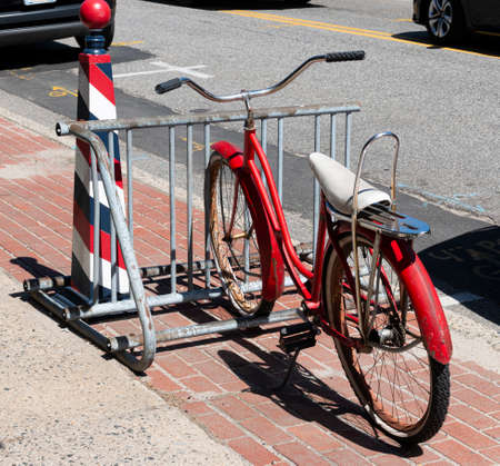 An old vintage red bicycle with a white banana seat parked in a bike rack on the sidewalk. Imagens