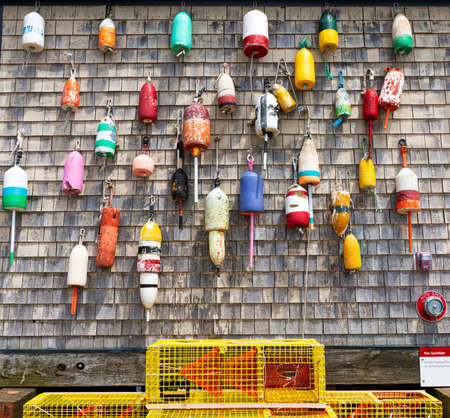 Vintage old colorful lobster buoys hanging on a weathered wall in Portand Maine with yellow traps on the bottom.