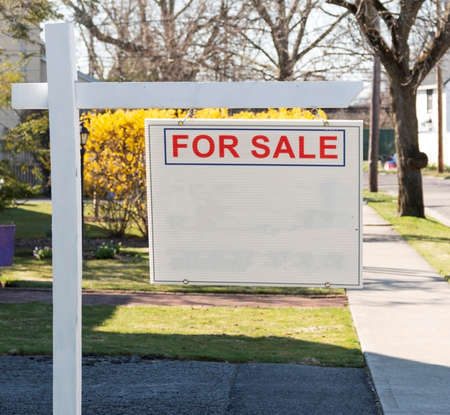 A wood post holding a sign that reads for sale with the rest blank on the front lawn of a residential home.