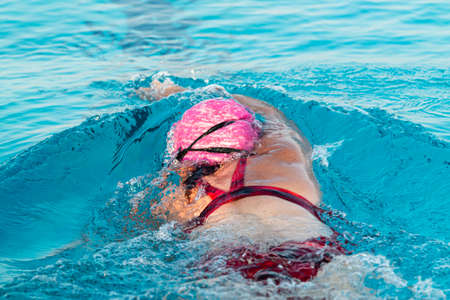 Rear view of a female swimmer in a pool pushing off of the wall splashing in the water while triathlon training.