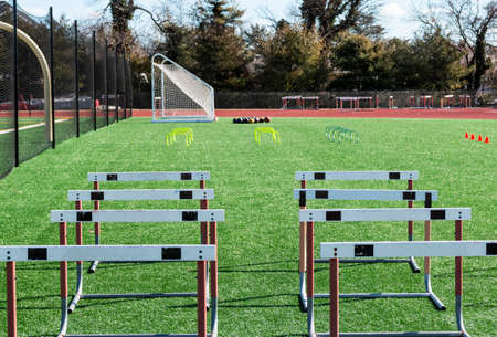 Track hurdles, mini hurdles medicine balls and orange cones set up on a green turf field for track and field strength and agility practice.