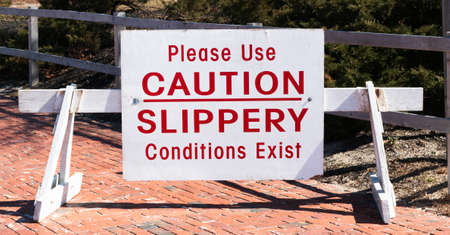 A large white sign on a wood barrier with red text reads please use caution slippery conditions exist at the entrance of a park on a sunny day.