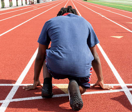 Rear view of a high school track and field sprint runner ready to run down the track in lane during practice.