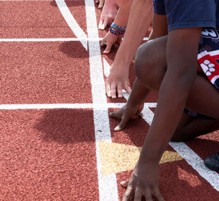Overhead sideview of hands and arms of high school boys ready to start a sprint race while at track practice.