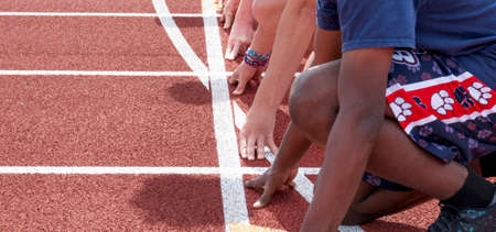 Side view of hands and arms of sprinter runners at the starting line ready to race at track practice