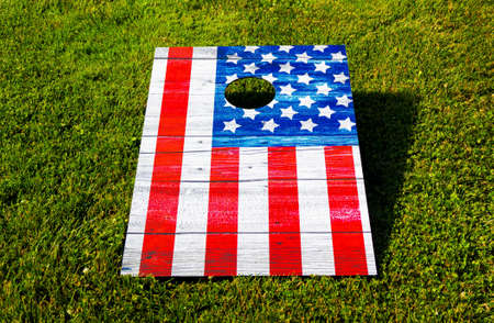 Red white and blue cornhole game looks like an American Flag on a green grass lawn.