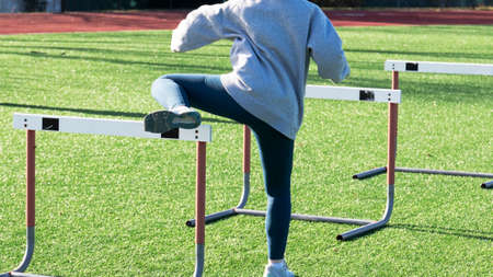 Rear View of a high school track runner performing hurdle trail leg drills on a green turf field.
