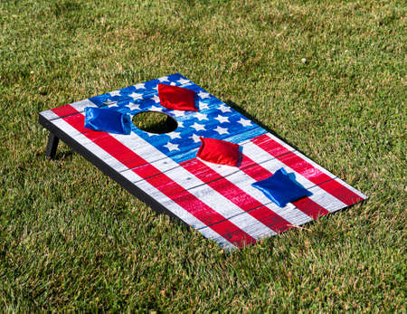 Red white and blue cornhole game with stars to look like an American Flag with bean bags.