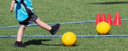 Preschool boy kicking a yellow soccer ball during practice with another ball and orange cones on the field. Stockfoto