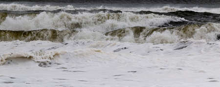 The atlantic ocean with extremely rough waves from a tropical storm off shore forming on top of each other.