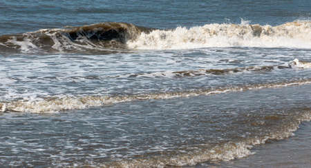 Calm Atlantic Ocean waves rolling on to the shore on the coast of Fire Island a barrier for Long Island New York.