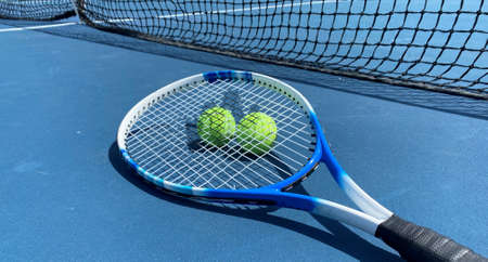 Horizontal view of Two tennis balls with a racket on top on a blue tennis court.