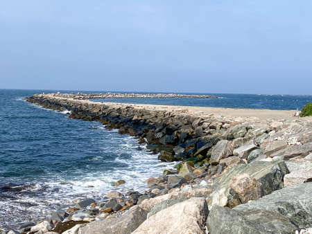 A fishing jetty of boulders extends into Narragensett bay at Camp Cronin Rhode Island. Stockfoto