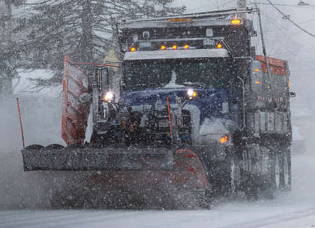 Close up of a municipal snow plow plowing the road during a snow storm in Long Islnad New York.