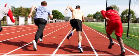Selective focused used to show the speed of four high school sprint runners starting a race at practice from behind. Stockfoto