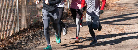 A small group of high school cross country runners running together on a dirt path uphill at Sunken Meadow State PArk.