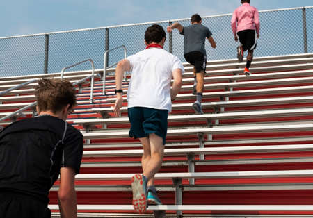 Five high school boys running up bleachers in a straight line, one at a time at summer camp pre-season workouts. Stockfoto