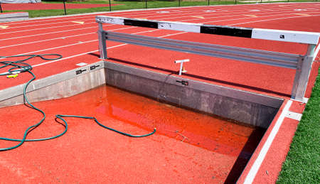 Empty steeplechase pit being filled up with water on a track from a green hose for for runners to compete.