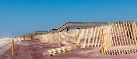 Horizontal view looking west on Fire Island at wood fences and walkways over the sand dunes protecting the summer homes on the Island.