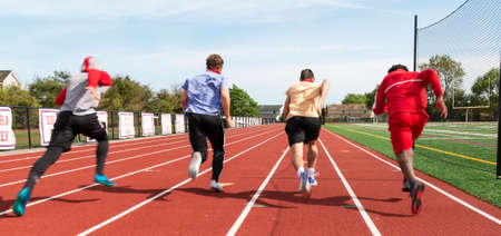 Rear view of high school boys sprinting down the track in lanes racing each other during practice.allowing some motion blurr to highlight their speed