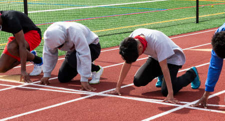 Four high school track runners on the starting line ready to compete in a sprint race at practice in lanes.